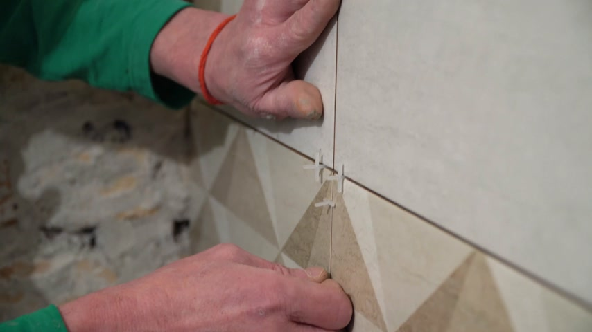 монтаж : Worker inserts plastic crosses in the seam between tiles. Finishing works, focus on hands. The technology of laying tile.
