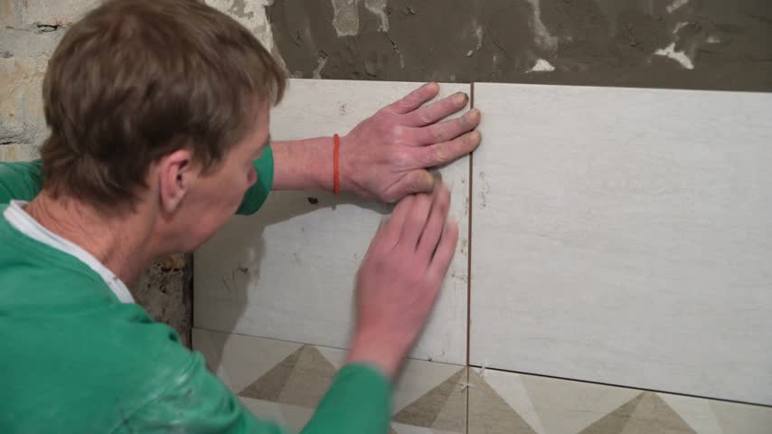 piastrellista : The worker puts the tiles on the wall. Finishing works, focus on hands. The technology of laying tile. Filmati Stock