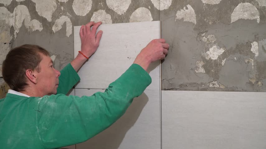 candida : The worker puts the tiles on the wall. Finishing works, focus on hands. The technology of laying tile. Stock Footage
