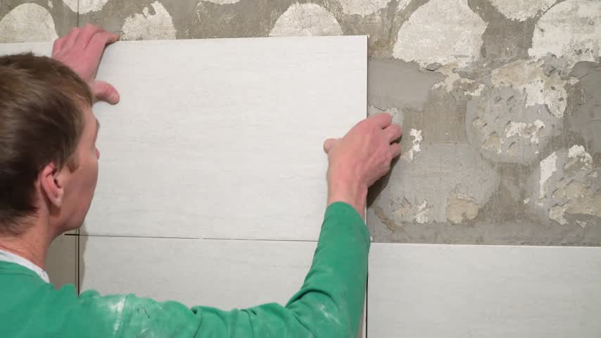 gesso : The worker puts the tiles on the wall. Finishing works, focus on hands. The technology of laying tile. Stock Footage