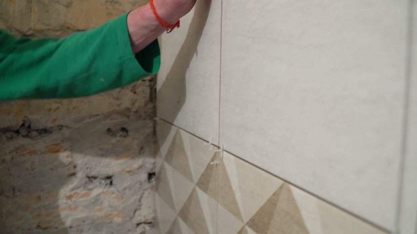 бежевый : Worker inserts plastic crosses in the seam between tiles. Finishing works, focus on hands. The technology of laying tile.