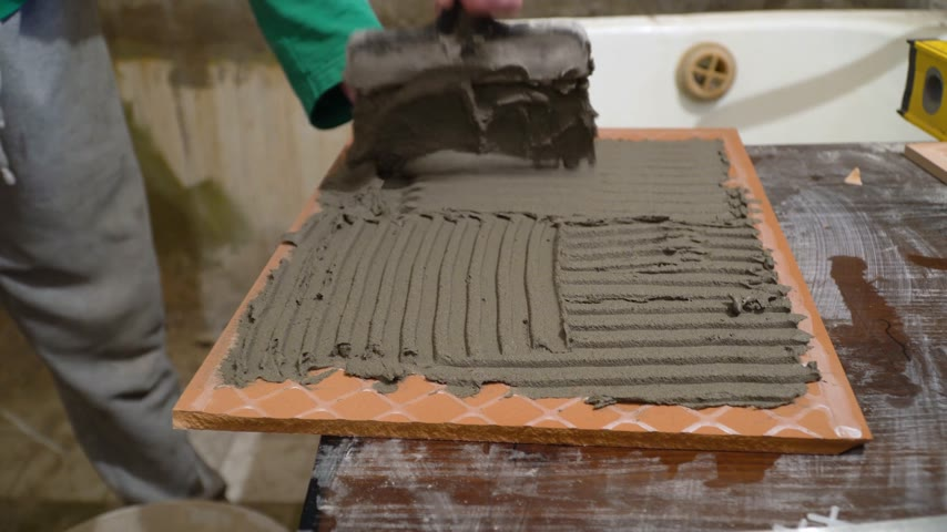 шпатель : Worker applies cement adhesive on the tiles. Finishing works, focus on hands. The technology of laying tile.