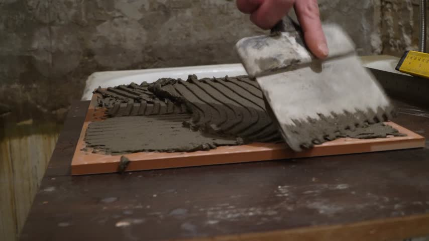 клейкий : Worker applies cement adhesive on the tiles. Finishing works, focus on hands. The technology of laying tile.