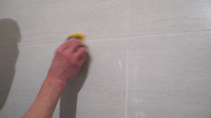 шов : Worker wet sponge rubbish the seams between the tiles. Finishing works, focus on hands. The technology of laying tile.