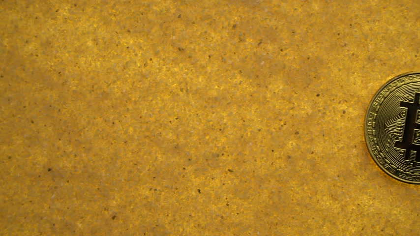 gömülü : one bitcoin crypto coin on a shiny golden sand background with backlight, top view. offset effect Stok Video