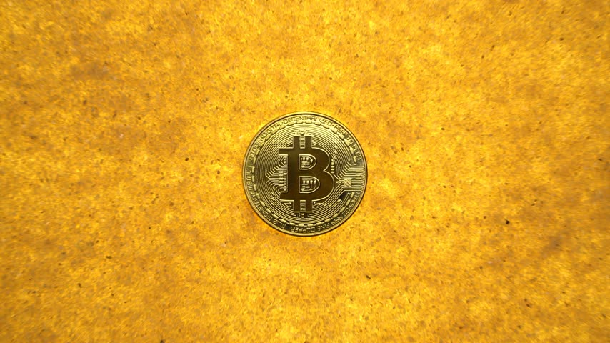 gömülü : one bitcoin crypto coin on a shiny golden sand background with backlight, top view. zoom effect Stok Video