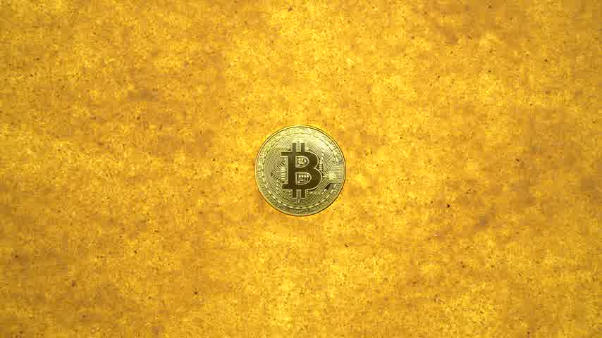 buried : one bitcoin crypto coin on a shiny golden sand background with backlight, top view. zoom effect Stock Footage
