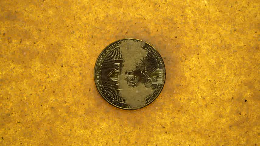buried : one bitcoin crypto coin on a shiny golden sand background with backlight, top view. blowing sand off coins Stock Footage