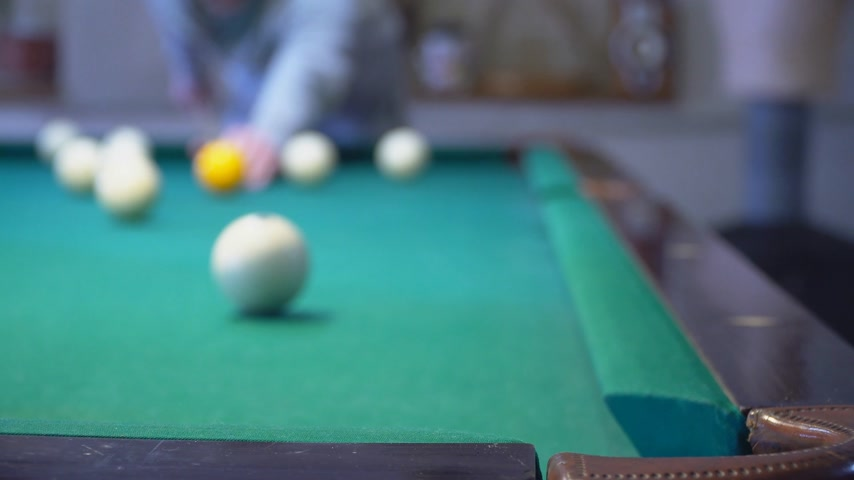 Green billiard table with white balls. Young man playing billiards. Selective focus Stok Video