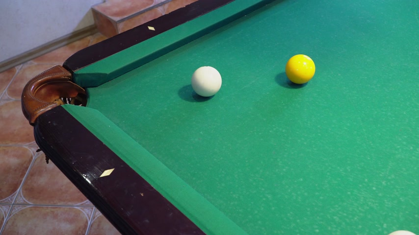 Green billiard table with white balls. Man playing billiards.