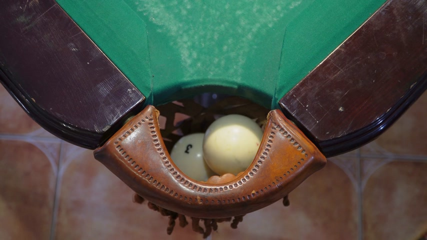 Green billiard table with white balls. Ball at the hole. Closeup. Top view Stok Video