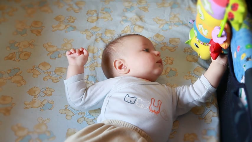 newborn child : Baby boy in bed playing with toys