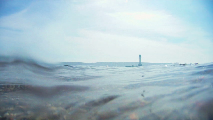 oceano : Underwater breaking waves with lighthouse on the horizon