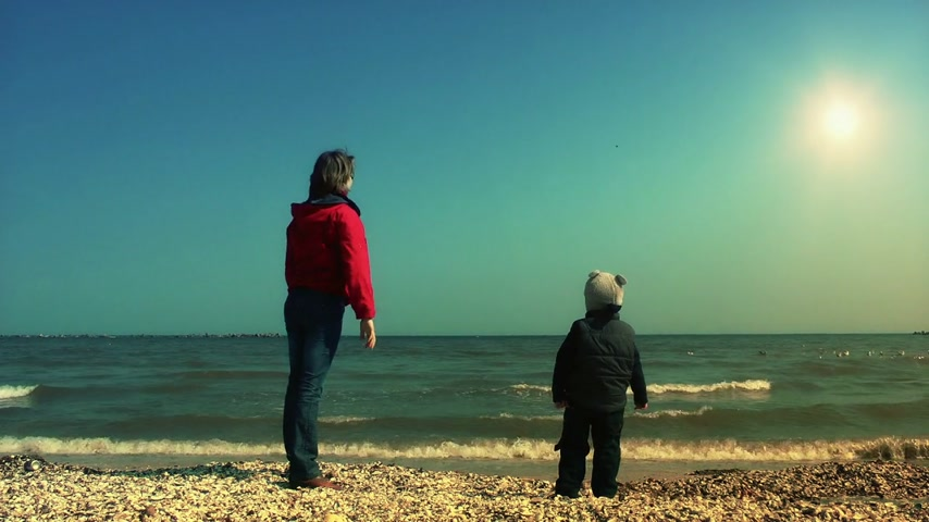 оболочка : Mother teaching her son to throw sea shells
