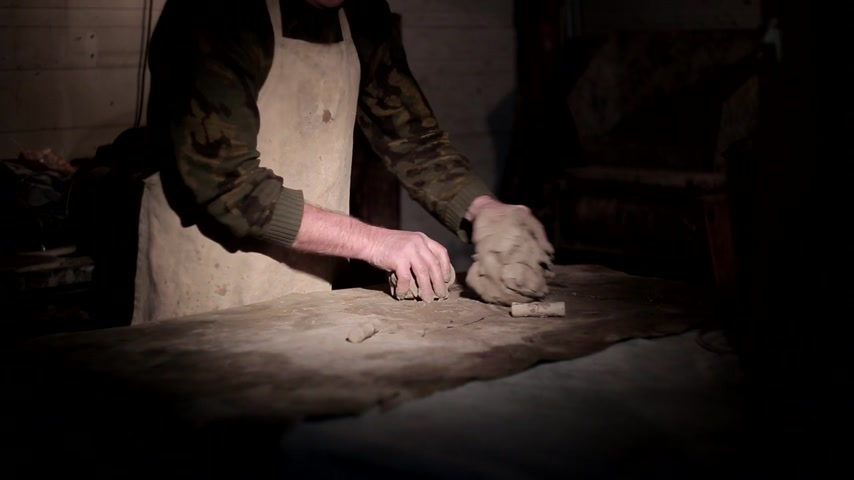 hrnčíř : Adult male potter master mashing the clay on table. Front view, closeup, hands only.