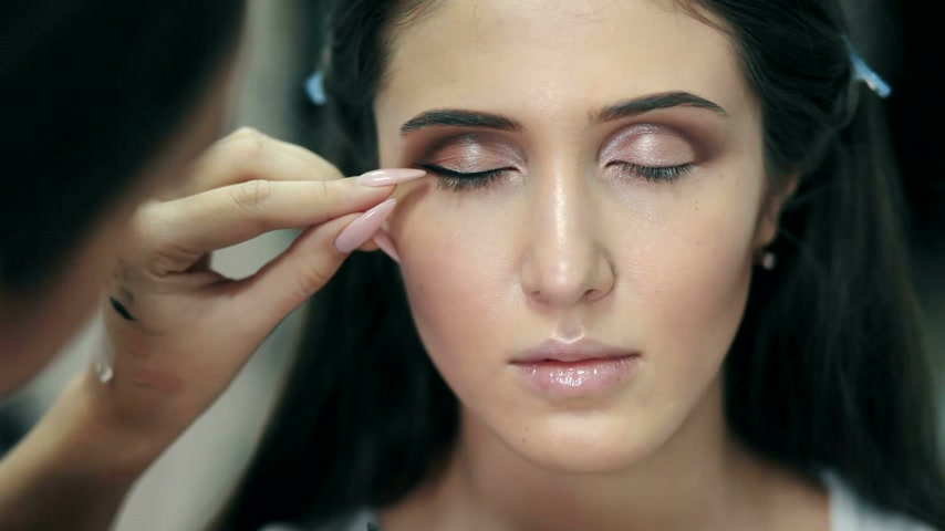 fashionshow : Make-up artist doing the make-up for beautiful girl Stock Footage