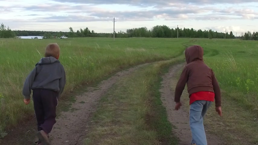 schooler : Two kids running together on rural road, slow motion Stock Footage