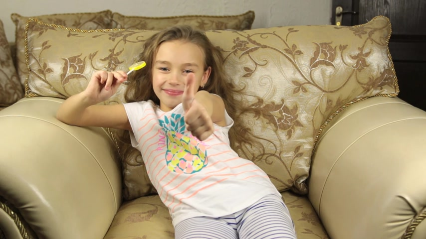 леденец : Girl licking candy on a stick in the form of lemon and raises the thumbs up. HD