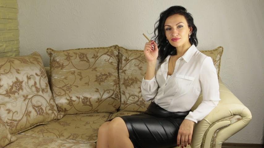papieros : Beautiful brunette businesswoman smokes, sitting on the sofa
