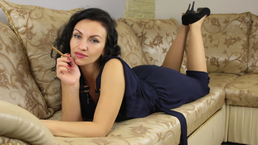 kötü : Beautiful brunette smokes while lying on a sofa. HD