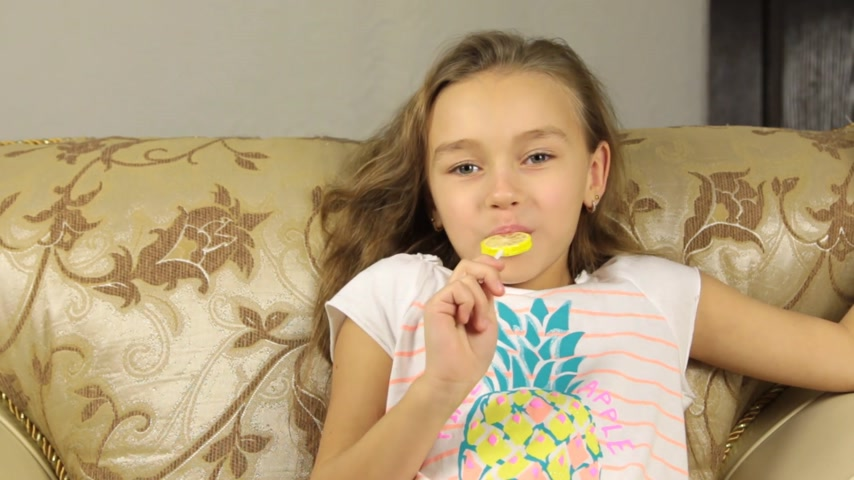 lambida : Girl licking candy on a stick in the form of lemon and raises the thumbs up.