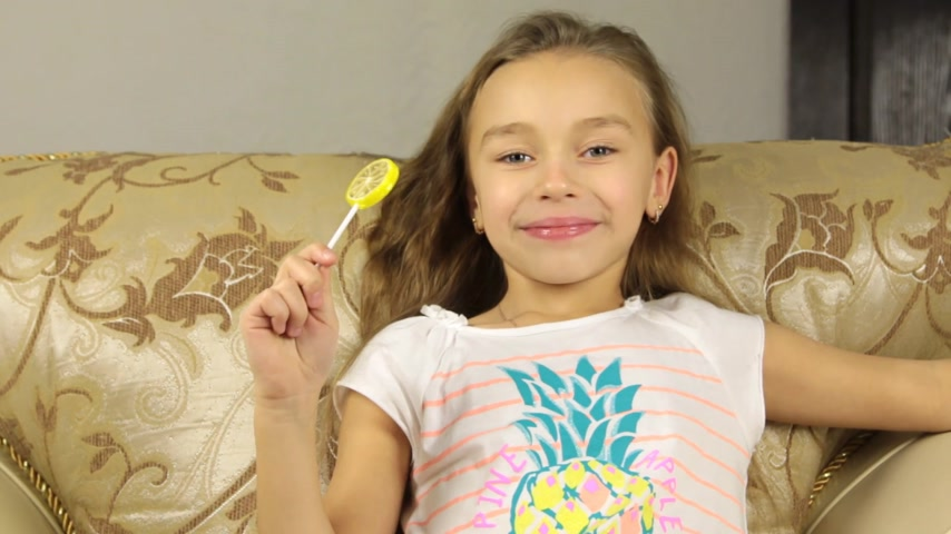 lambida : Girl licking candy on a stick in the form of lemon and and smiling Vídeos