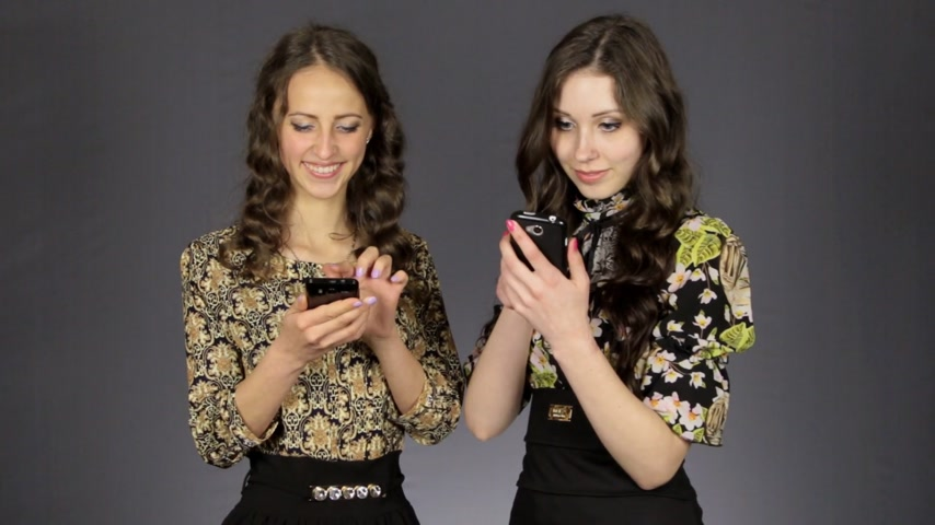olhares : Two beautiful girls look at the phones screen