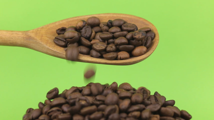 peeled grains : Wooden spoon pours coffee beans at heap of coffee beans on a green screen Stock Footage
