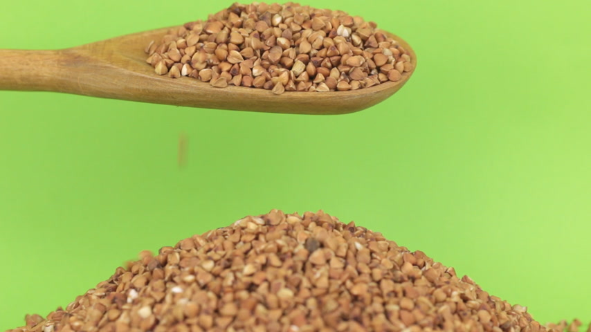 peeled grains : Wooden spoon pours grains buckwheat at heap of buckwheat on a green screen