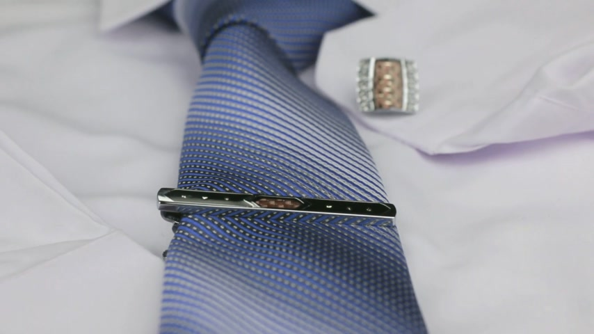 eleganckie : Dolly shot, focus on blue tie, cufflinks, clasp, white shirt.