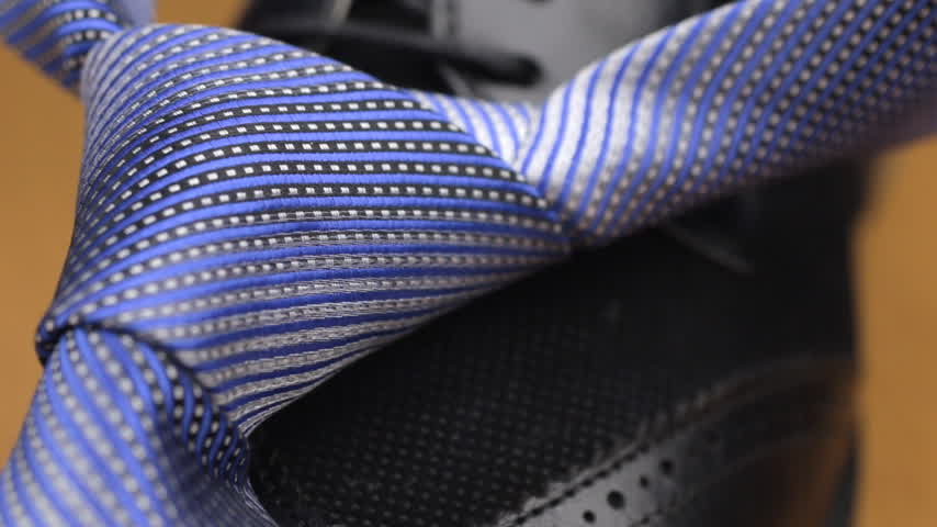 knotted : Blue knotted tie lies on a black mens shoes. Stock Footage