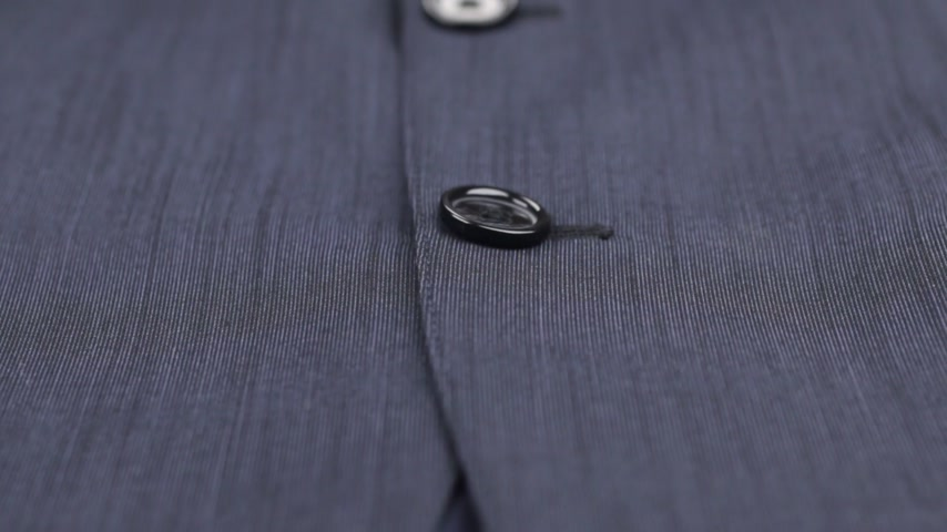 přezka : Close-up of buttons on a blue suit. Dolly shot.