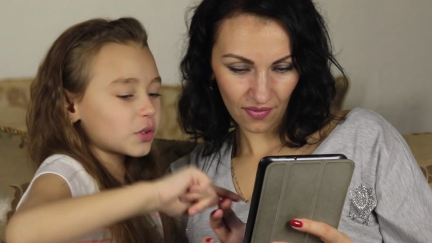 lánya : Approximation, zoom, daughter teaches mother to play the game on the tablet. Stock mozgókép