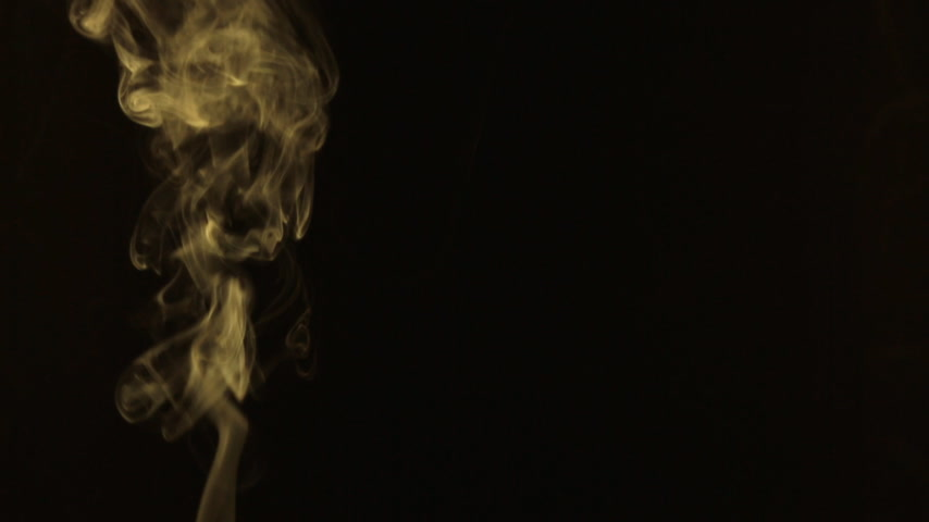 incenso : Beautiful stream of yellow smoke turns into swirls on a black background.