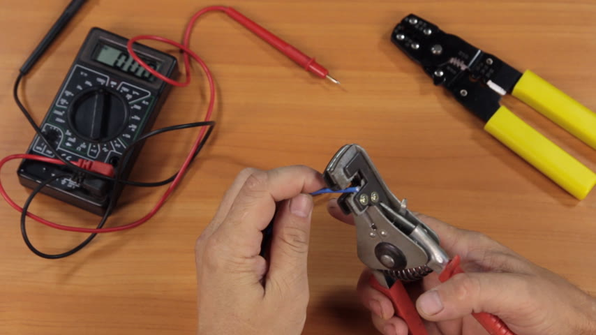 wire stripper : Master electrician removes insulation from copper wires with a special tool. Stock Footage