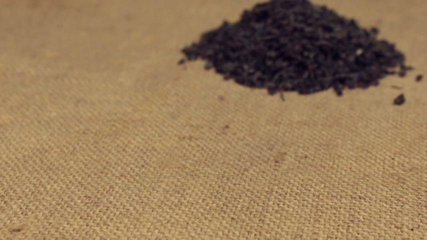 len : Zoom, approaching is a pile of dry leafs black tea lying on burlap. Close-up Stock mozgókép