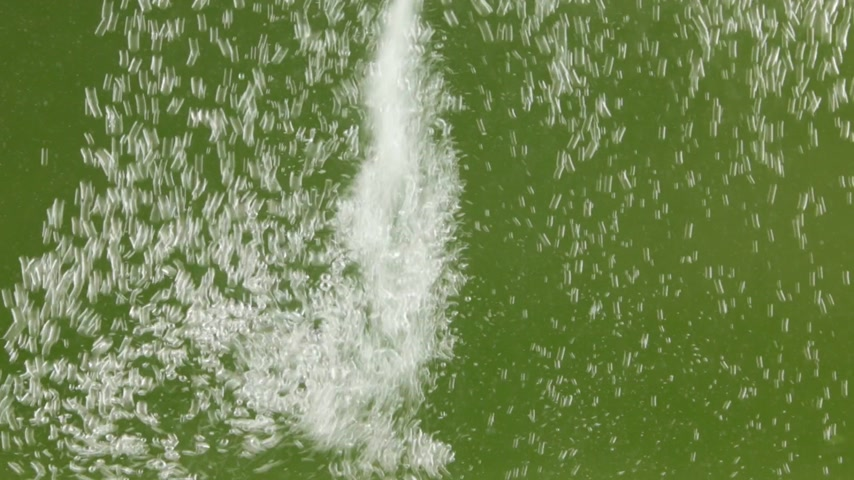 acqua pura : Stream of white bubbles in green water. Pouring water splashes and creates turbulent bubbles.
