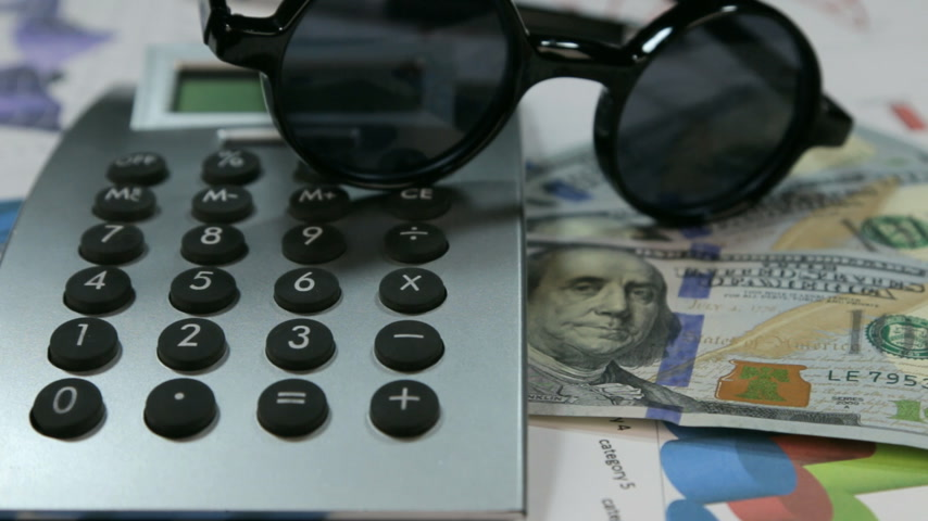 налоги : Sun protective hipster glasses lie on the calculator and dollars. Rotation. Стоковые видеозаписи