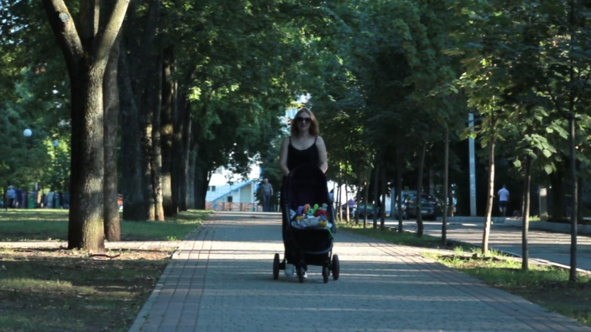 lánya : Mom with daughter, lying in a stroller on an evening walk. Urban landscape.