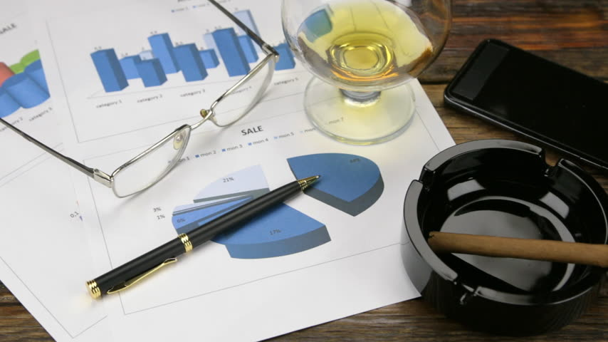 papeteria : Rotation, business and finance concept of office desk, glasses, glass, cognac, chart, phone, pen, ashtray, cigar.