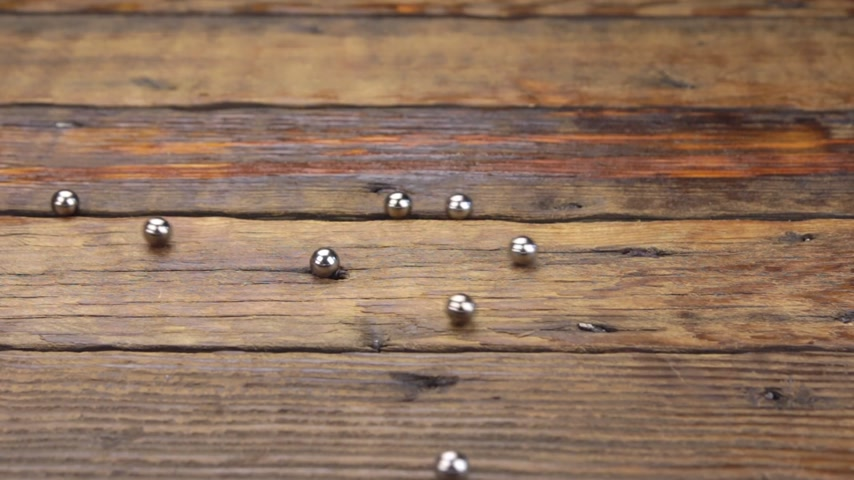 kurşun : Iron balls rolling randomly along a vintage wooden table. Concept