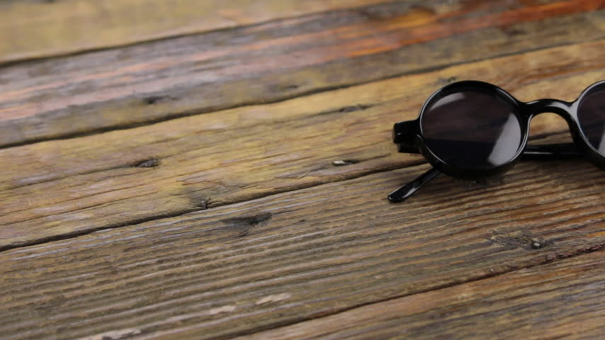 single shot : Slider shot. Close-up sunglasses on wooden table. Stock Footage