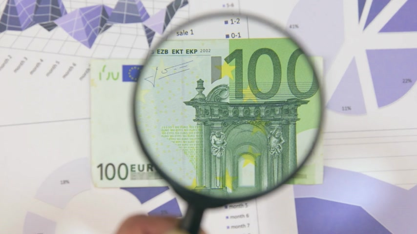 scrutiny : Study of a banknote one hundred euro, increasing with the help of a magnifying glass.