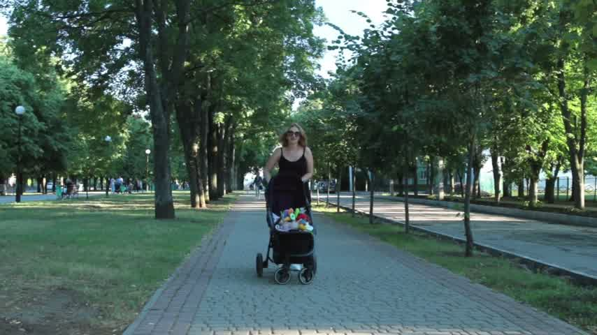 wozek dzieciecy : Mom with baby, lying in a stroller on an evening walk. Urban landscape.