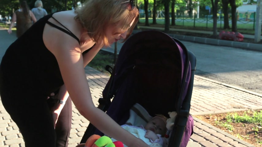 кукла : Mom plays with the baby lying in a pram on a walk.