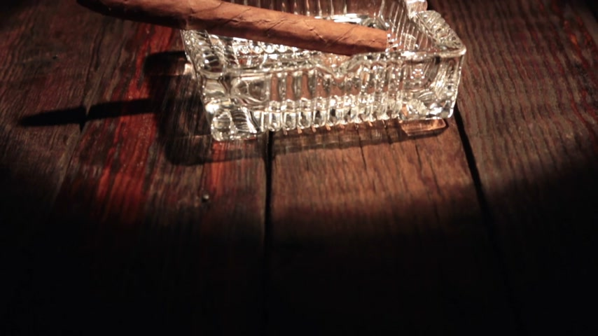 изделия из дерева : Vertical panorama of a cigar lying in a black ashtray in the beam of light.