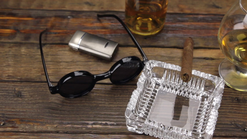 виски : Luxurious cigar, glass of alcohol and stylish sunglasses on a vintage wooden table. Panorama.