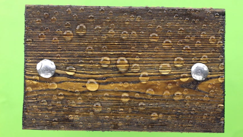 szegecs : Wind blows on a dark wooden plank with iron bolts in drops of rainwater.