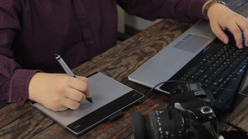 using stylus : Close-up. Designer works on a graphics tablet. Retouching on computer laptop