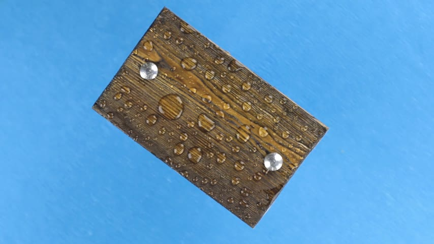 perçin : Wind shakes drops of water on a rotating wooden board with iron bolts, isolated on blue.